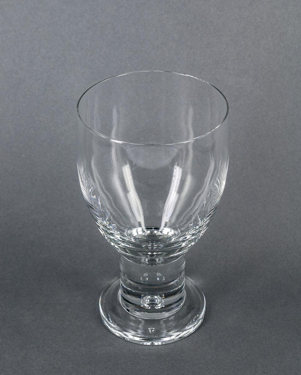 Ölglas i halvkristall. Servisglas, design Gunnar Cyrén. Halvoval kupa på tjockt cylindriskt ben med luftkula nedtill. Halvtjock fot.