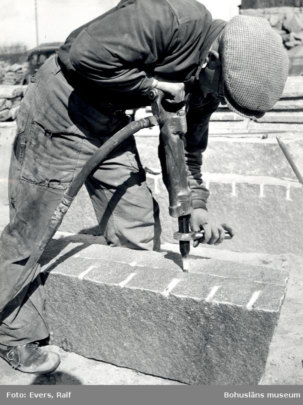 En man borrar i ett granitblock för att klyva det, i fickan har han en tumstock
