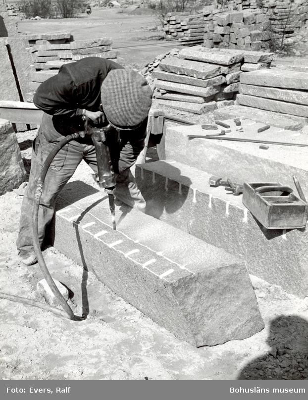 Stenhuggare borrar i stenblock för att sedan klyva det