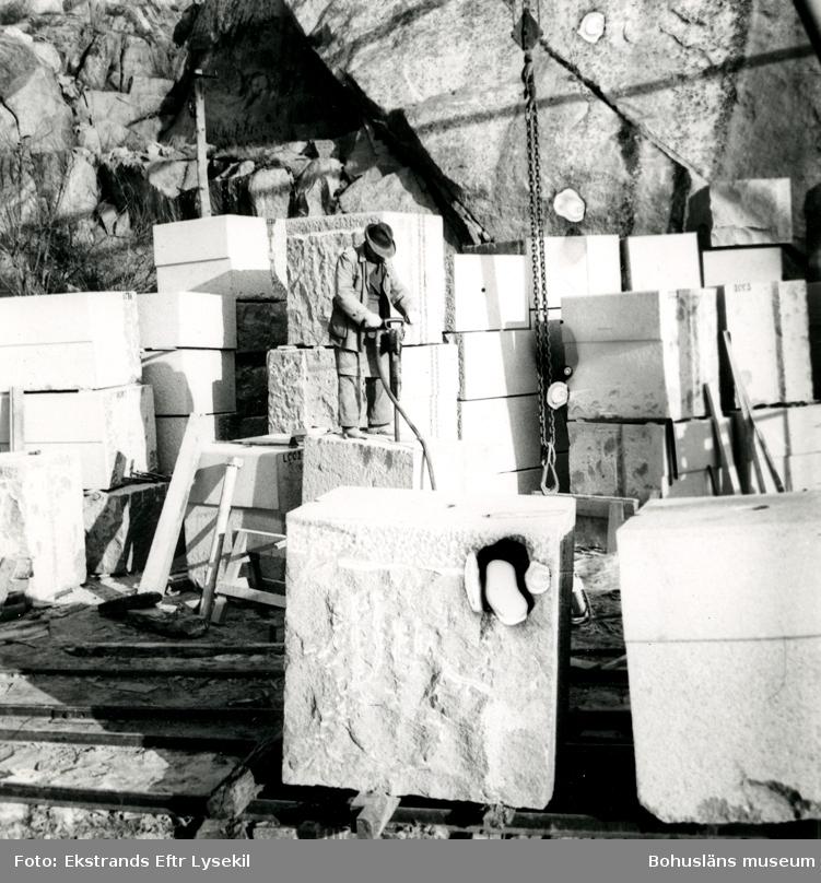 Stenhuggare står uppe på ett stenblock och borrar