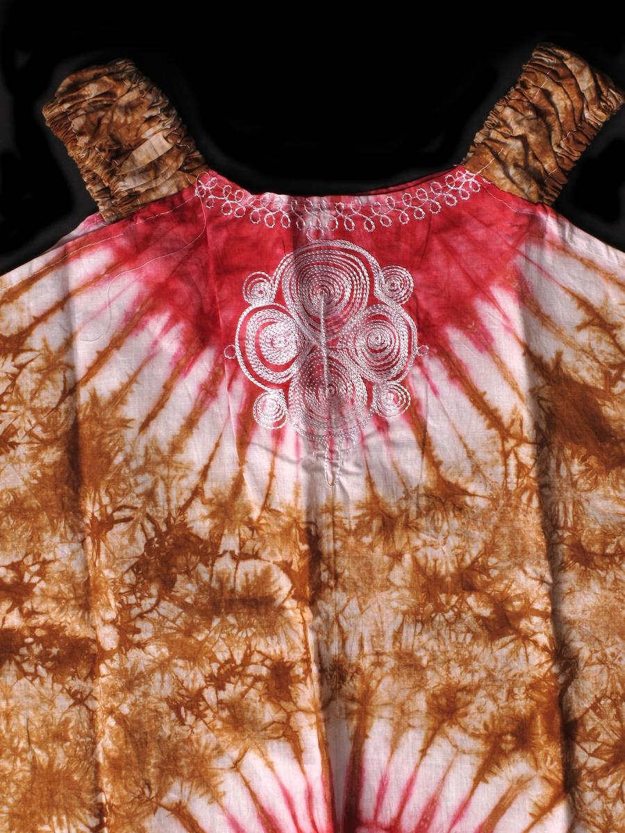 """Ermeløs fortsid kjole til voksen i hvitt med batikkmønster i rødt og kanelbrunt.  Kjolen har en stor """"sol"""" i rødt midt foran og bak, samt en tilsvarende ved halslinningen både foran og bak.  Hvite broderier rundt halslinningen.  Broderi foran på brystet med fire fylte sirkler med fire mindre sirkler mellom, som del av en bord rundt de førstnevnte.  Kjolen skrår jevnt fra under armene og ned til hemmen, og har ikke legg eller kiler.  Skulderstroppene har strikk i løpegang.  Svært enkelt lagd, og med en del løse tråder og stygg sying. Sømmene er ikke kastet eller faldet opp, bortsett fra nederste kanten på skjørtet."""