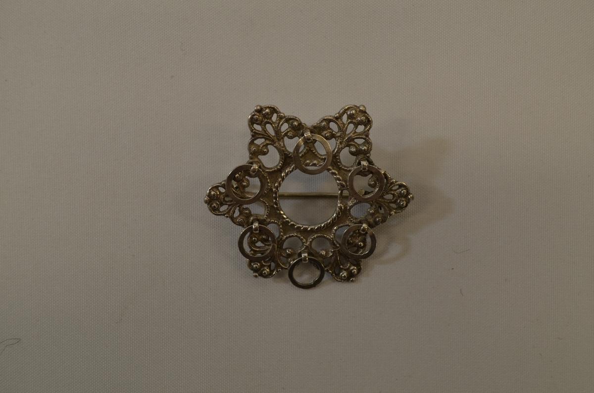 Sporesølje (spiresølje) støypt i sølv med seks spir og seks ringar. Nål og krok pålodda på baksida.