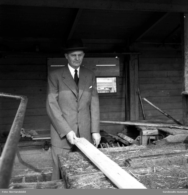En man i hatt, kostym och slips pratar med en arbetare i såghuset på Skönviks sågverk.