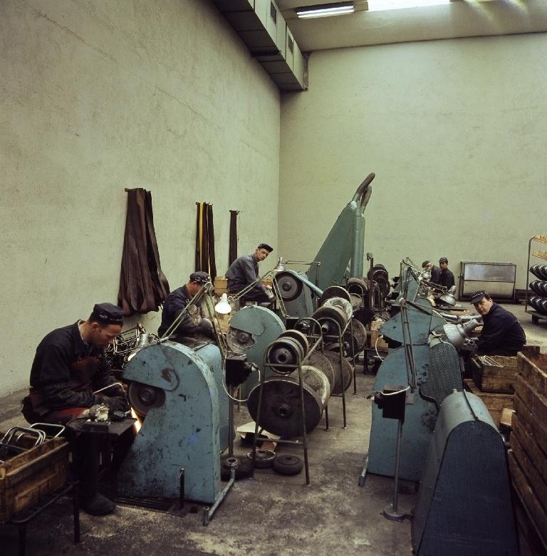 """Arbeidere sitter ved slipemaskiner og sliper deler før lakkering og fornikling i sliperiet i bygningen """"Nr. 11"""" til sykkelfabrikken til Jonas Øglænd AS på Sandnes."""