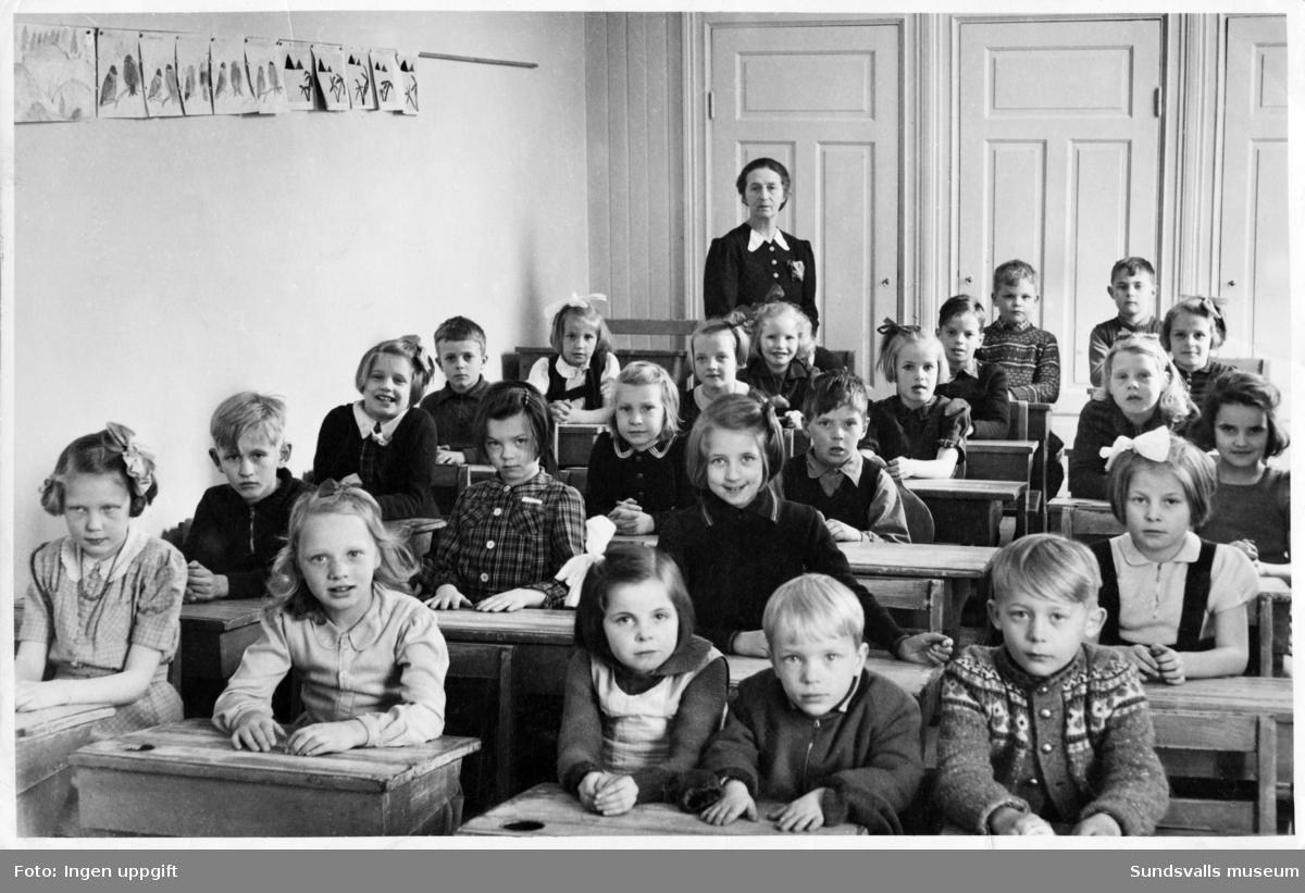 Första klass i Gustav Adolf-skolan hösten 1942. Fröken Hagelin står längst bak i klassrummet. Man hade även lektioner i Yrkesskolans lokaler eftersom militären använde Gustav Adolf-skolan under krigsåren.