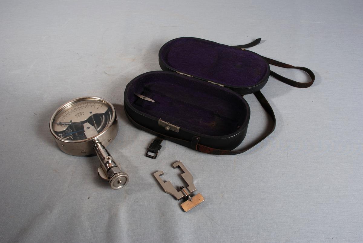 Rundt manometer med hals og justeringsskruer, holder med festeskrue hører til. Manometeret ligger i ovalt etui med lukking på siden og bærerem festet på sidene. Etuiet er foret med tekstil, i lokket er det vatt under foret.