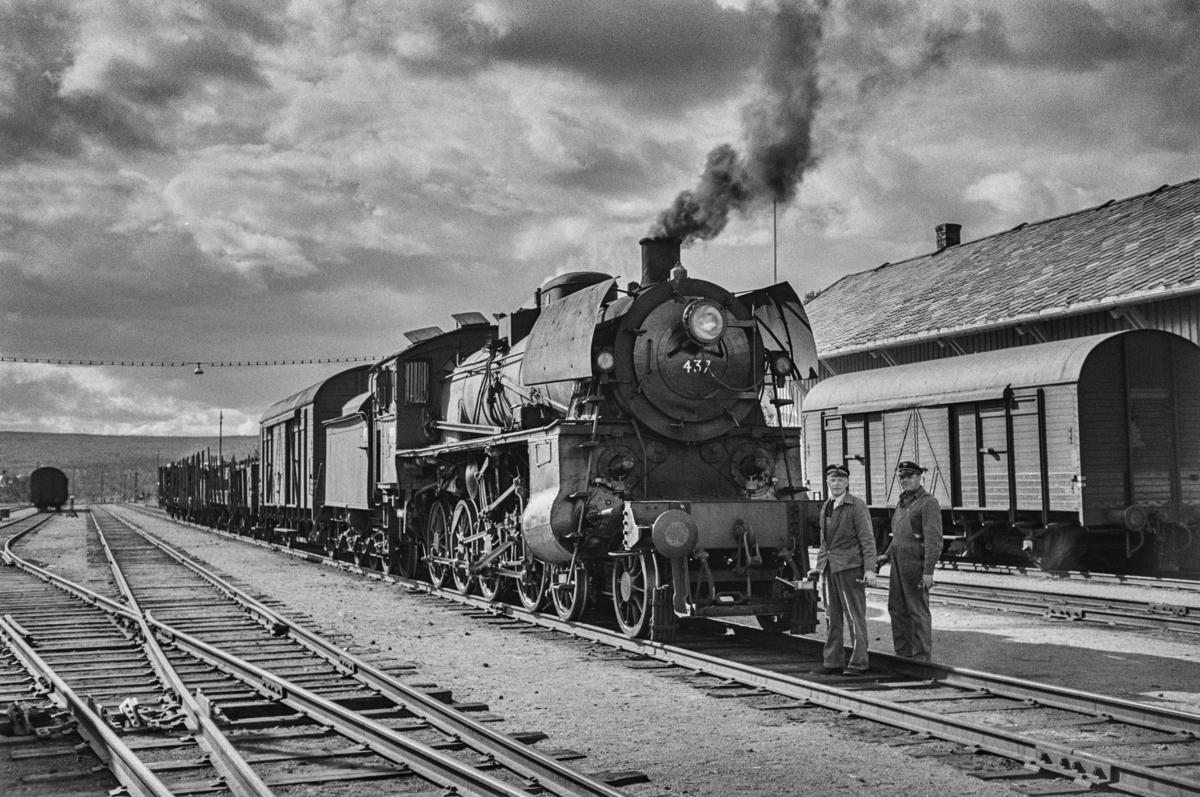 Tjenestegjørende lokomotivpersonale foram damplokomotiv type 26c nr. 437 i sydgående godstog på Røros stasjon.