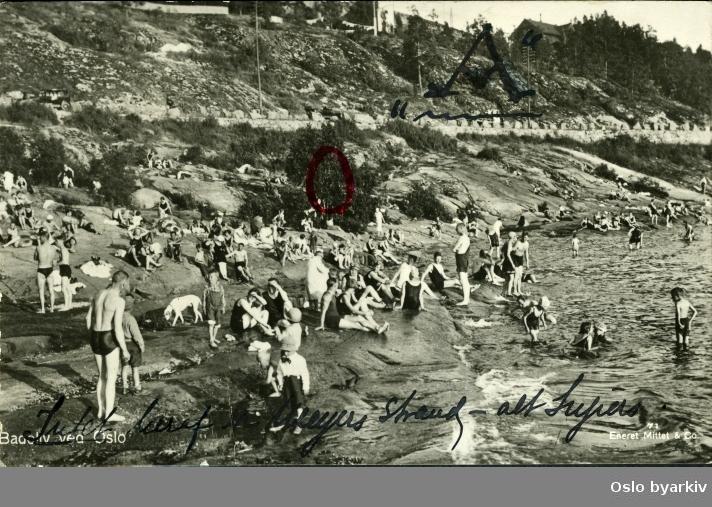 """Katten badestrand (kommunal badestrand 1931). Badende mennesker fra svaberg langs den 200 m lange stranda. Kantstein langs (gamle) Mosseveien. Antagelig i begynnelsen av 1930 årene. Postkort med påskrift: """"Intet heraf er Meyers strand- Ingiers."""" Stor A og rød ring i bildet."""