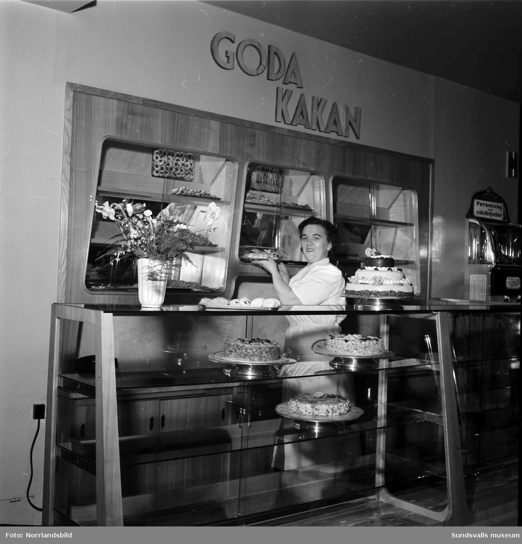 """Bageri """"Goda kakan"""" i EPA-varuhuset på Storgatan 25. Ett biträde fyller på disken med tårtor och andra godsaker. Strategiskt placerad till höger i bild syns en personvåg med viktbiljett."""