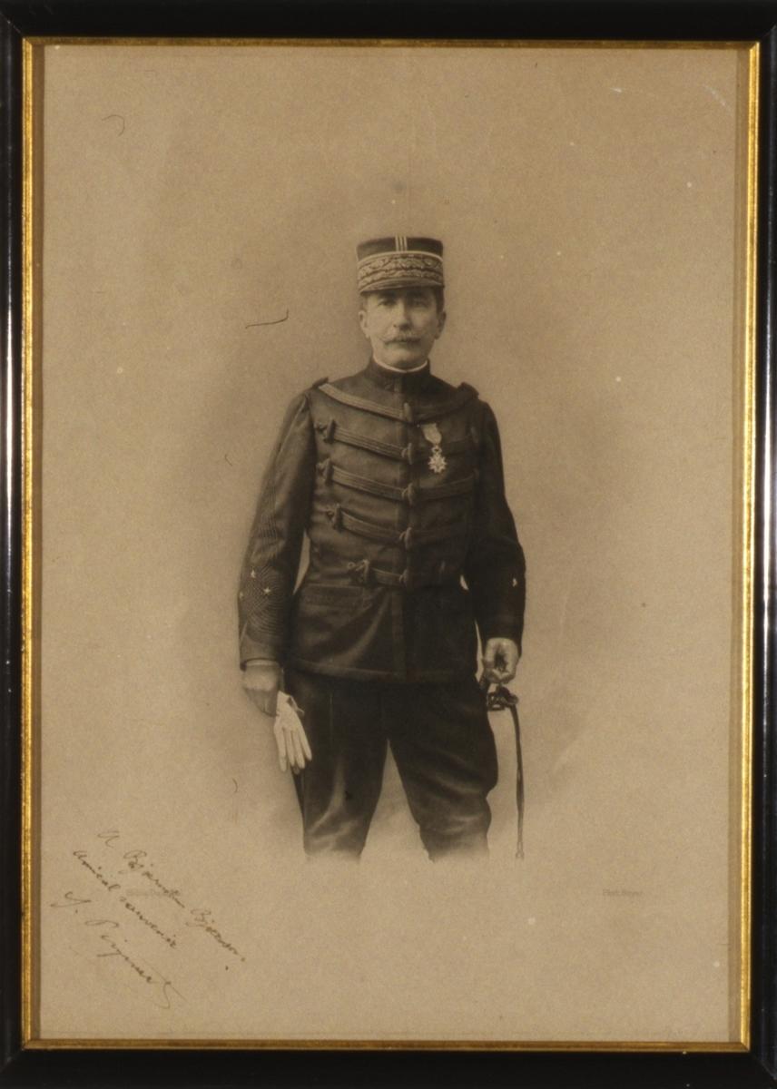Stående mann i paradeuniform, avskåret ved knærne.