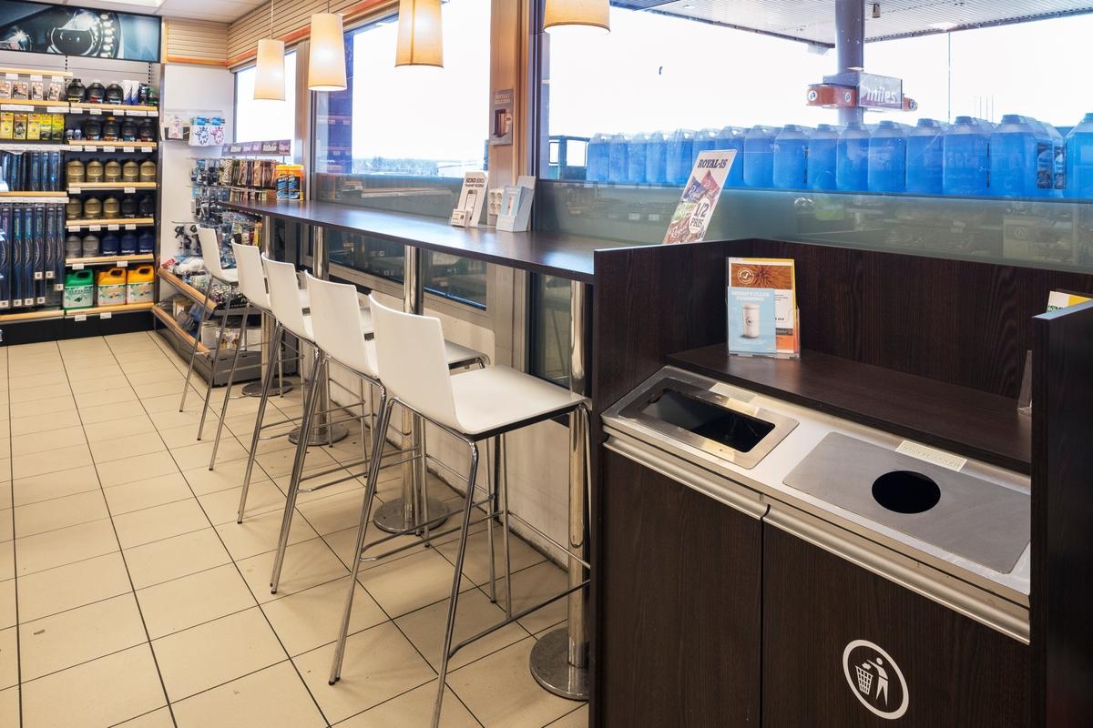 Statoil Dal. Butikk interiør kafedel med høye stoler og en lang bordplate langs vinduet. Seksjon for håndtering av søppel fra kafeområde.