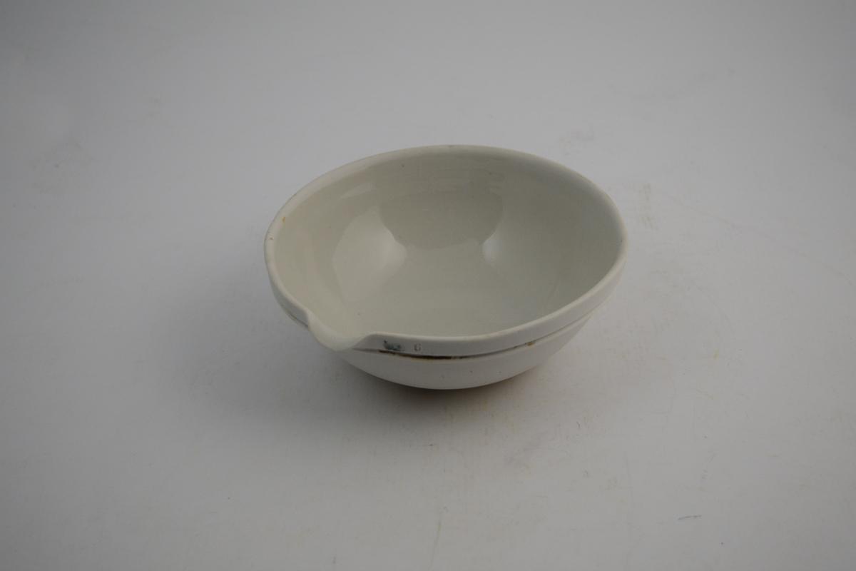 Sirkelformet hvit porselensskål med helle tut. Glasert inni og ca. 5 cm fra kanten utenpå - resten utenpå er uglassert. Skålen ble brukt til produksjon av legemidler, kanskje på vannbad.