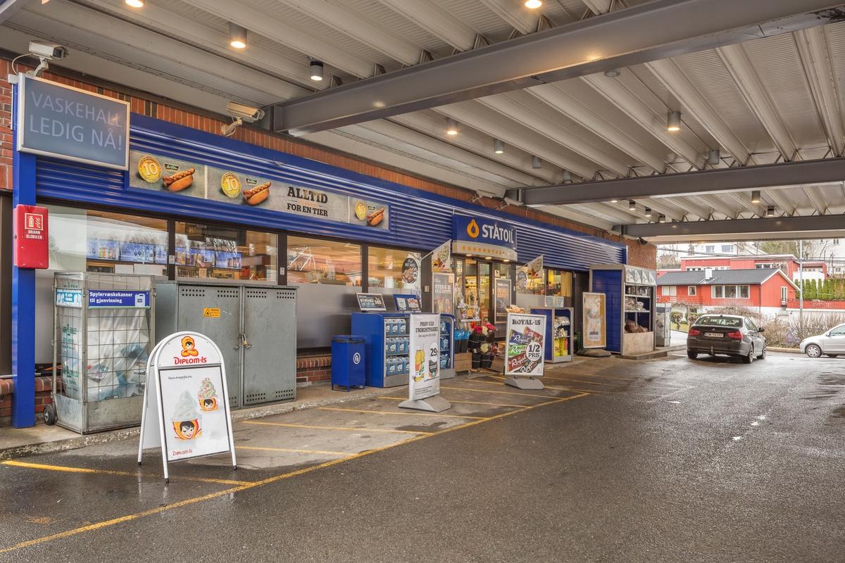 Statoil Nadderud. Inngangspartiet til butikken under pumpetaket. Reklameskilt og Statoilskilt. Dunker med spylerveske.