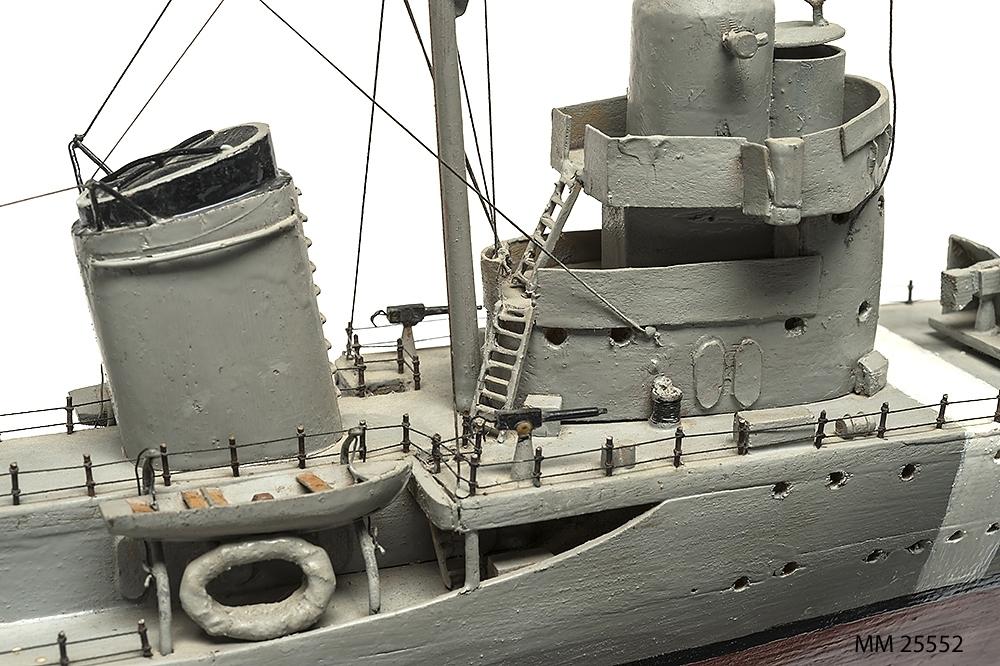 """Tämligen grovt tillverkad fartygsmodell, huvudsaklingen gjord av trä. Fartyget är jagaren Mode som är målad grå över vattenlinjen och med röd bottenfärg. Klassiskt jagarskrov med upphöjd back. På fördäck står en kanon i öppen lavett och på akterdäck två likadana pjäser. Två luftvärnspjäser på en upphöjd brygga. En skorsten med svart topp. Slingekölar på båda sidor i rött. På bogen är siffrorna 29 målade. Alldeles för om bryggan och akter om den aktra pjäsen finns vita neutralitetsband målar över däck och ner längs skrovets sida till den svarta vattenlinjen. Fartyget har två propellrar. Bryggan är öppen. Modellen står på en fernissad platta av mörkt trä med hjälp av två profilerade små """"pelare""""."""