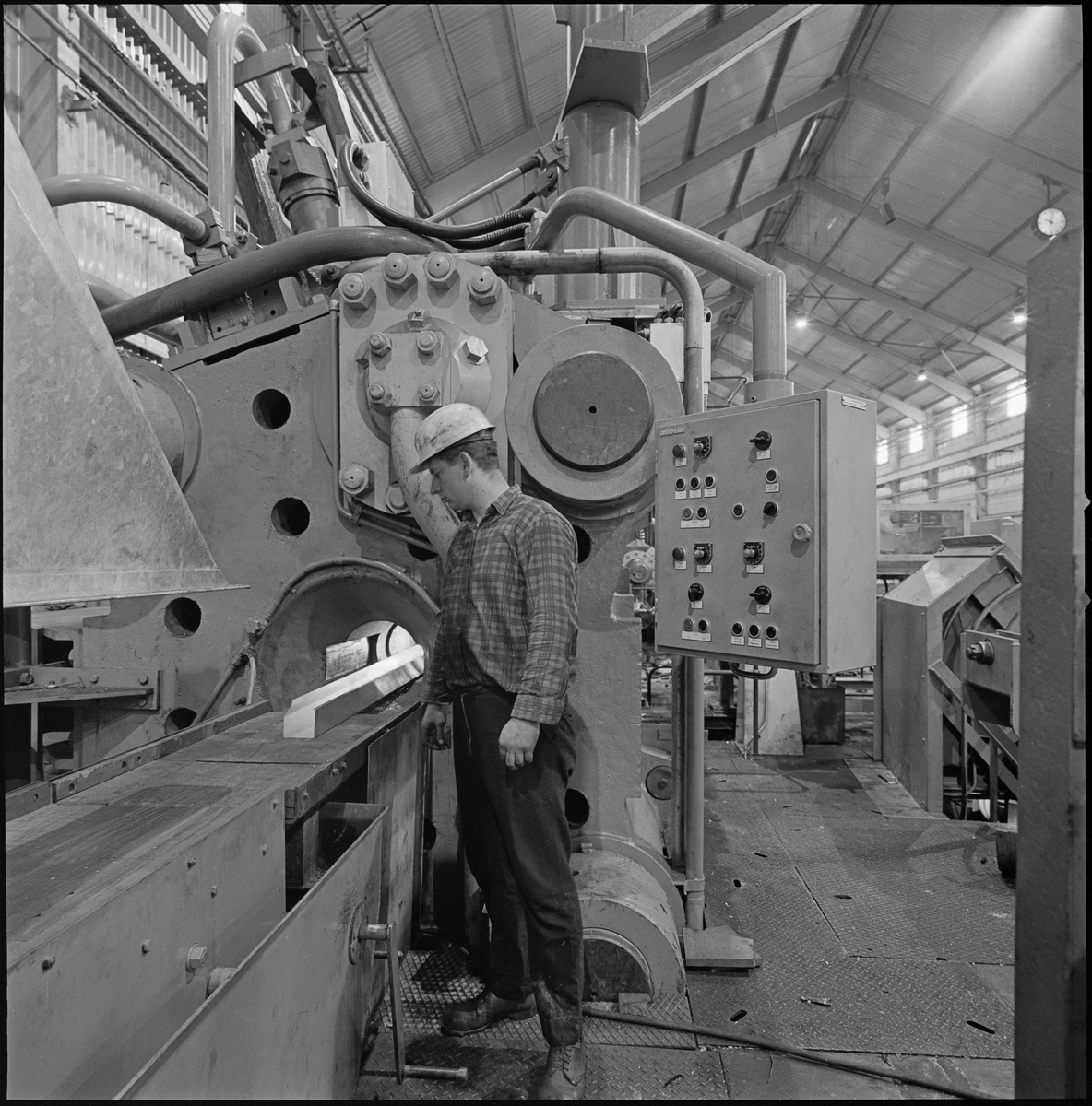 En mann følger med på et aluminiumsprodukt på et bånd på Norsk Hydro sitt aluminiumsverk på Karmøy.