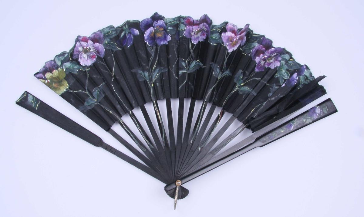 Av sort silke, avklippet i kanten, litt tunget øverst. Spiler av sort tre. På vifteflaten er malt naturalistiske stemorsblomster og blader. Stilkene fortsetter nedover på spilene.