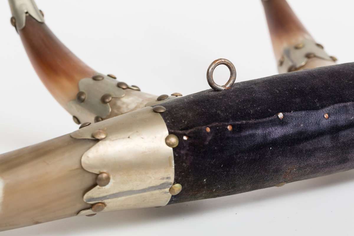 """Knaggrekke antagelig håndlaget av kuhorn. 4 horn/kangger. Montert med """"dekorative"""" beslag som er spikret og dekornaglet på hornene. Kledd med cordfløyelstoff på midtparti. To øyeskruer på toppen for feste til vegg."""