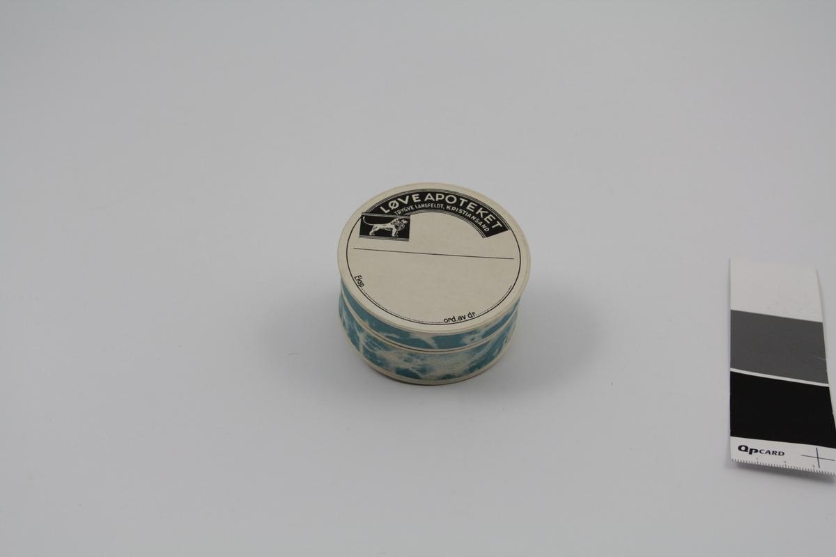 Sirkelformet eske med lokk. Alle deler i papp. Blå farge. Brukt til oppbevaring/salg av tabletter og dosert pulver.