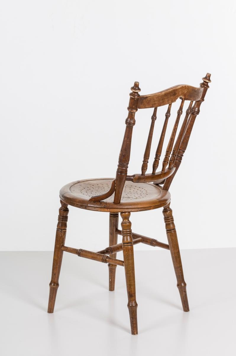 Stol i lakket treverk. Rundt stolsete med hullemønster. Rygg som er svakt buet med spiler og mønster. Dreide ben om spiler i rygg.