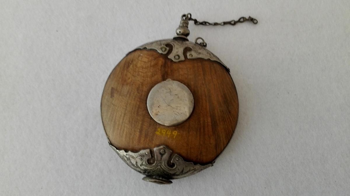 Form: Flattrykt, rund, dreia av lauvved og vakkert sølvbeslått. Kjøpt 7/6 1899 på Øye i Lærdal.
