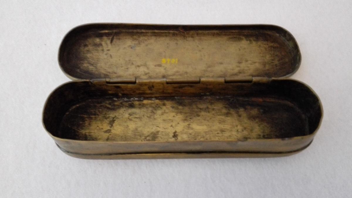 1 messing tobaksdaase.  En avlang tobaksdaase av størrelse og form som en almanakdaase. Længde 15,2 cm, bredde 4,5 cm. Avrundet i endene. Under bunden raat indridset AIST.  Kjøpt av Daniel Wallem, Sørheim.