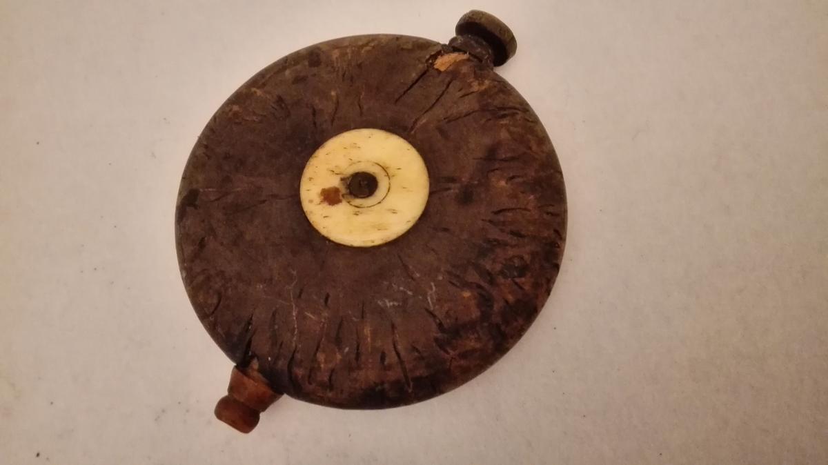 Form: Sirkelrund, med flattrykka sider. 1 snusflæske.  Cirkelrund, dreiet snusflæske av birkeri, flattrykt paa siderne. Paa midtens begge sider indfældt dreiete benknapper, tut av ben. Diameter 8,5 cm.  Kjøbt av Jens Sørebø, Ortnevik.
