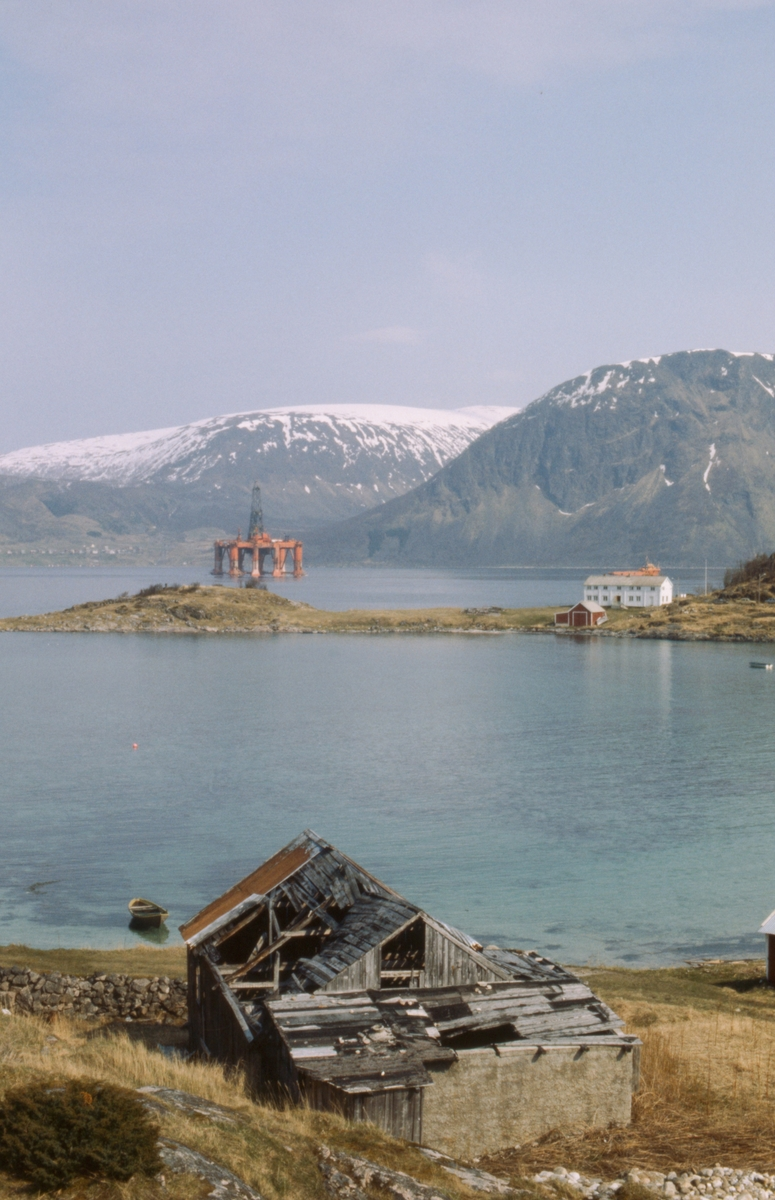 "Oljeplattformen ""Treasure Seeker"" under slep.  Gammel bygning på Elgsnes i forgrunnen."