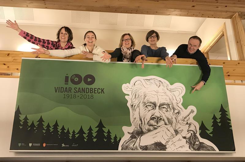 Ansatte ved Kulturkontoret i Åmot kommune bak banner med Vidar Sandbeck-jubileet. (Foto/Photo)