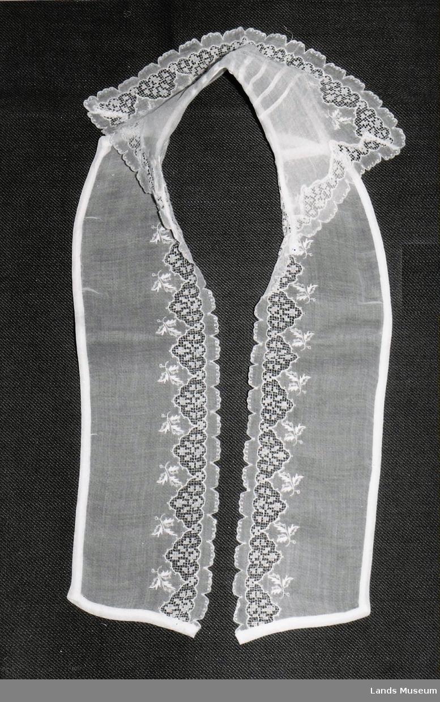 Påsydd krage med slag. Bak på kragen er det lagt inn små legg. Kragen har små slag. I ytterkanten på kragen og fram på sjalene er det blonder.