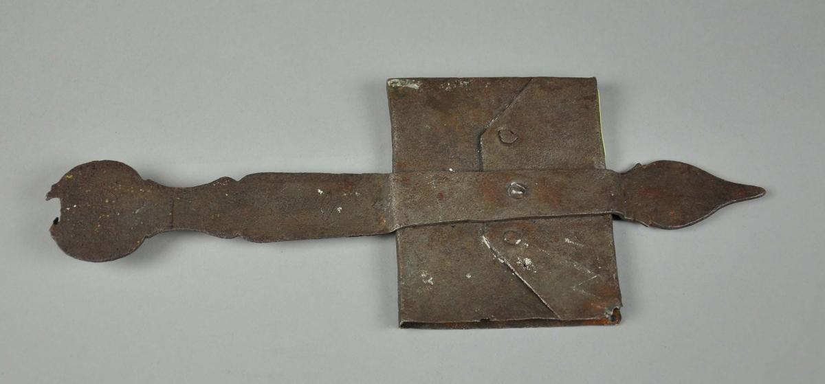 Rektangulær lomme i smijern med hulrom for å legge inn en beskjed. Lommen er festet til en stang som er dekorert utformet.