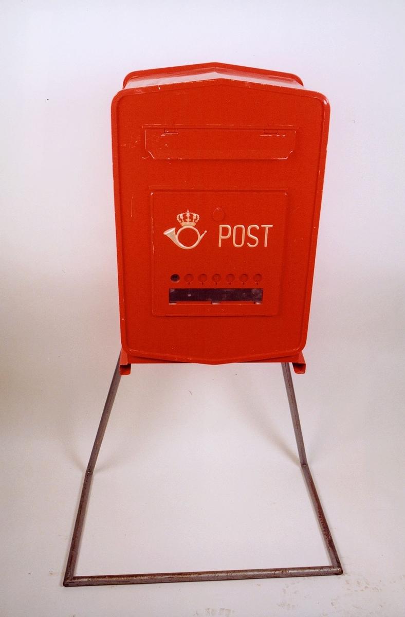 Rød mekanisk tømmepostkasse for tømmeapparat. Med posthornemblem og ordet Post i gul farge. Med felt for tømmetider og markering av når tømt