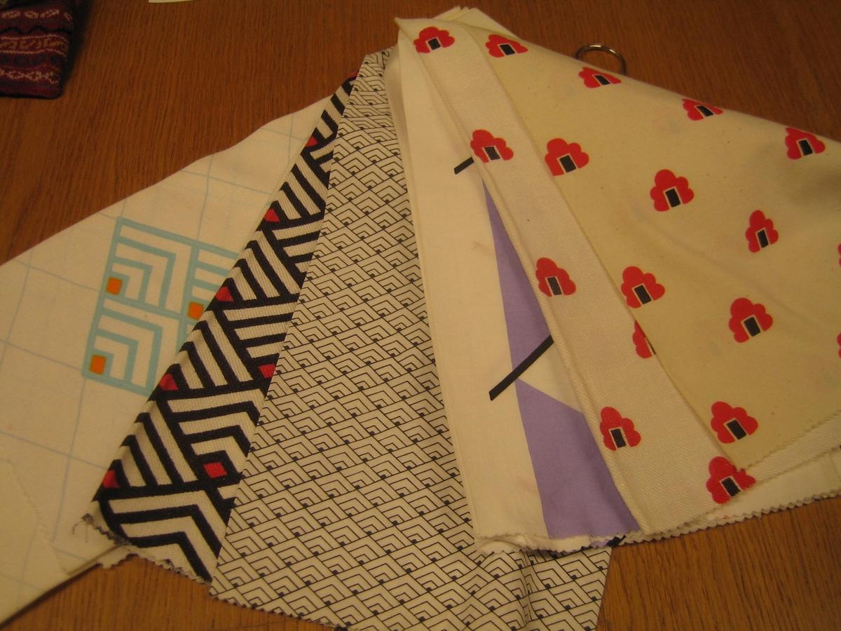 På draperiet är det tryckt stänkta fläckar i svart och lila.