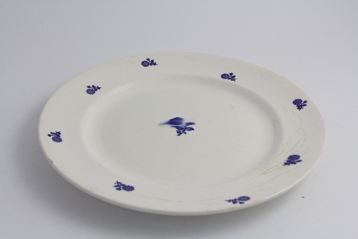 Rundt serveringsfat. Hvit bunn med dekor i trykte blå blomster. En noe større blomst i midten, åtte blomster på fanen.
