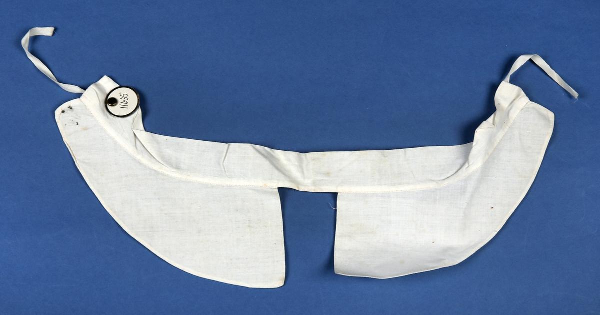 Løskrage, lerretsvevd, lett stivet. Knytebånd festet 2 cm innpå halslinningen bak.