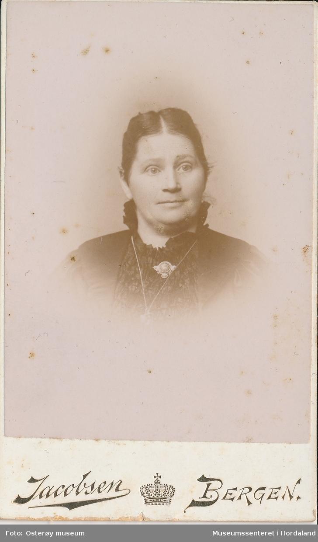 portrettfotografi av kvinne med midtskill, mørkt hår smala i nakken, mørk kjole med brosje og kjede i halsen
