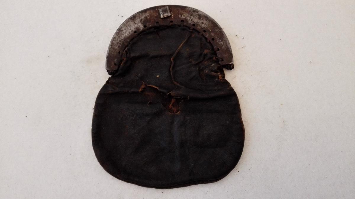 Skindpung med jernlaas.  Defekt skindpung med 2 rum og jernlaas, hvis bredde er 11,5 cm.  Pungens længde 16,7 cm. Gave fra gaardbr. Ove Lysne, Lærdal.