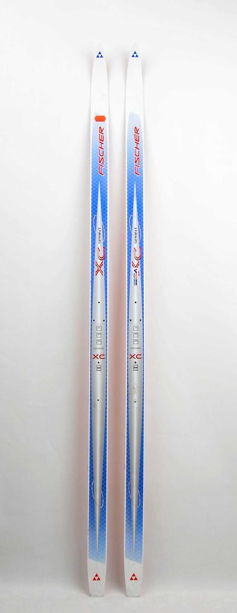 Langrennski for barn laga av glasfiber, med såle av raud plast. Kvit, sølv og blå overside. Det har vore bora hol til bindingar.