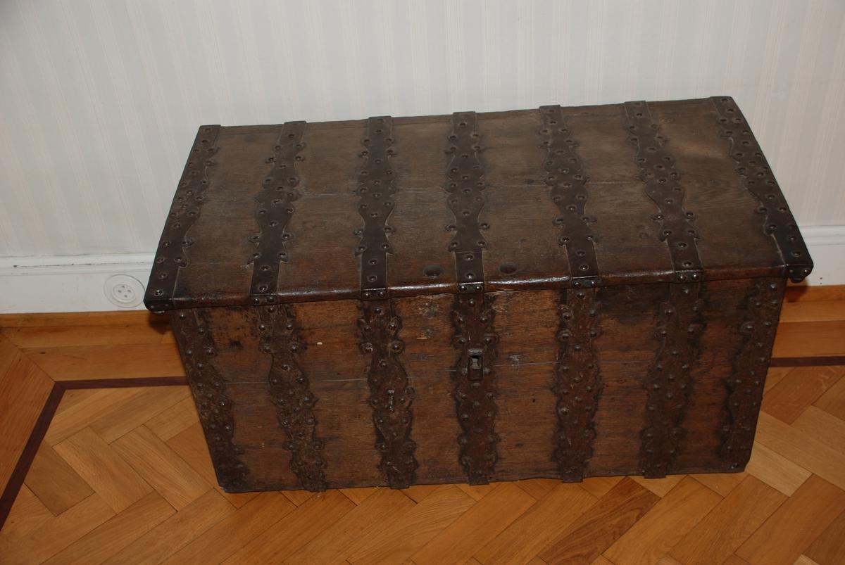 Kiste med rike jernbeslag. Flatt lokk, sidene svakt utadhellende oppover.
