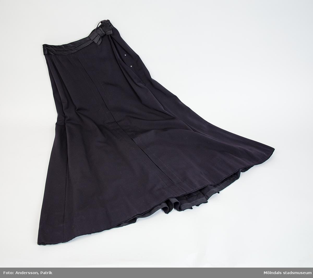 Kjol i svart yllegabardin med tre veck bak. Ett draperat duschessband med rosett i midjan och fodrad med bomullstyg. Omsydd.
