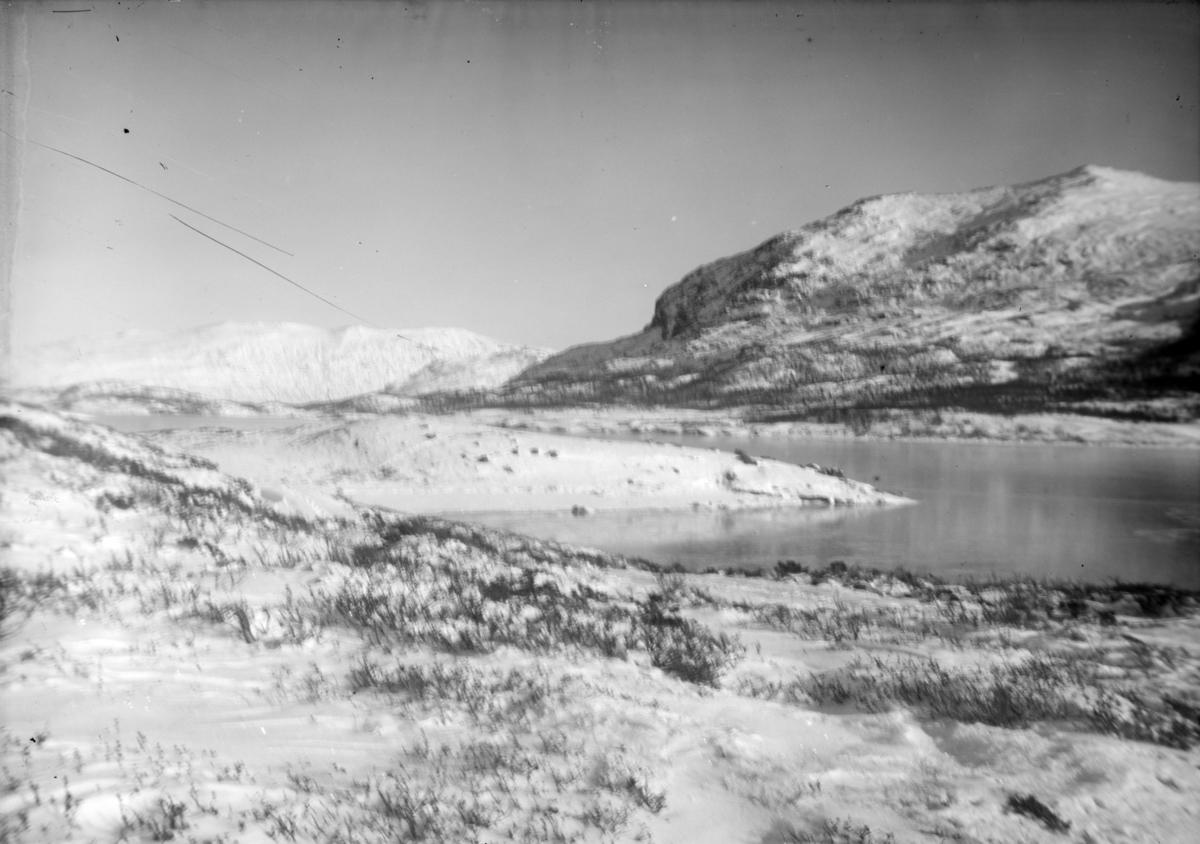 Uklart bilde av fjellandskap med islagt vatn