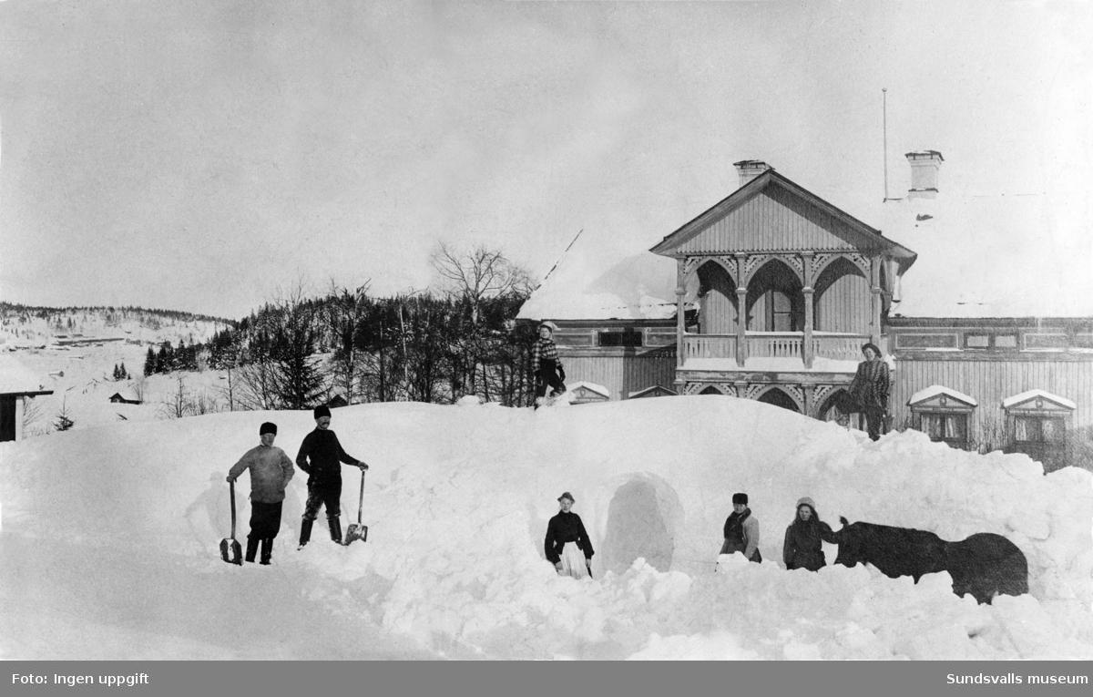 """Gården """"Katrinelund"""" i stadsdelen Haga en snörik vinter 1907. Makarna Wictor och Anna Sundqvist (og. Söderqvist) var innehavare av hemmanet Byn 3 på vars mark stora delar av Hagaområdet anlades. Den andre mannen från vänster med spaden är Wiktor Sundqvist och uppe på snöhögen står Anna Sundqvist. I mitten av bilden syns en snögrotta. Gården finns ännu kvar (2017) och ligger på Malmgatan 23."""