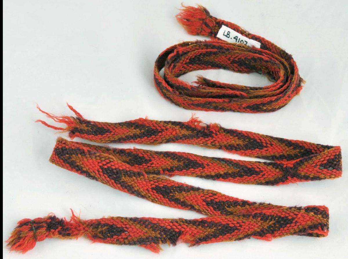 Slengde sokkeband laga av 8 trådar raudt, 8 trådar fiolett og 6 trådar okegul. Små frynser i begge endar.