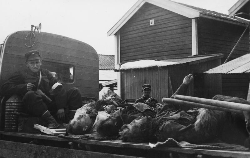 Omkomne fraktes vekk fra slakterikjelleren. Fotograf ukjent/Glomdalsmuseets fotoarkiv.