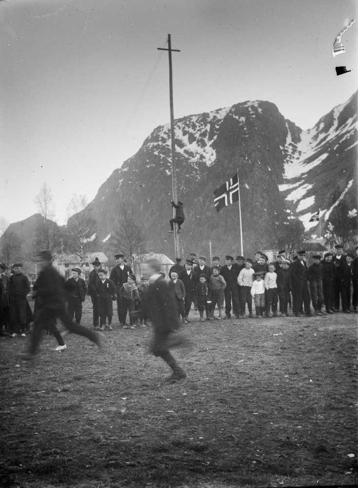 17. mai-leker i skolegården-kappspringing-publikum-flagg-klatrestang. Trangskaret i bakgrunnen.