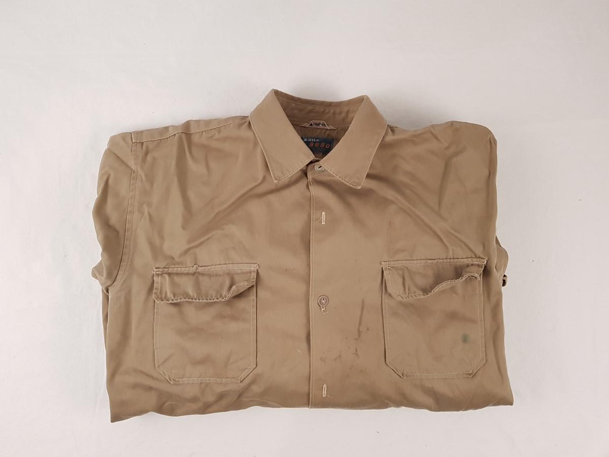 Uniformen består av jakke, bukse, beret, skjorte, slips, armbind, belte, gamasjer og støvler.
