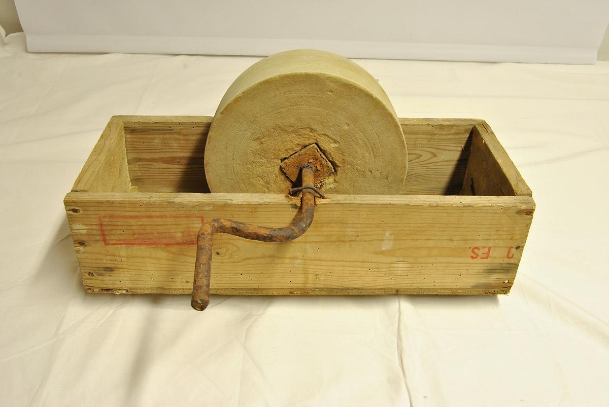 Slipestein med vannkar og håndtak med sveivemekanisme. Vannkaret er i tre. Har et hjemmelaget preg. Slipesteinen haldes på plass med to spiker.