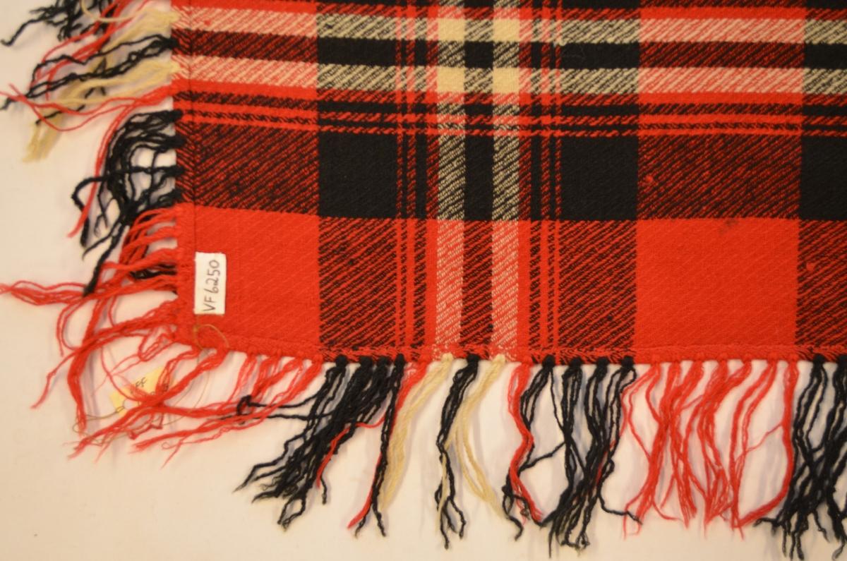 Sjal i ruta kypertvove ull i raudt, svart og sauekvitt. Sett saman med av to stykker med saum på midten. Falda langs kantane og, og sett på frynser i same fargene som sjalet.