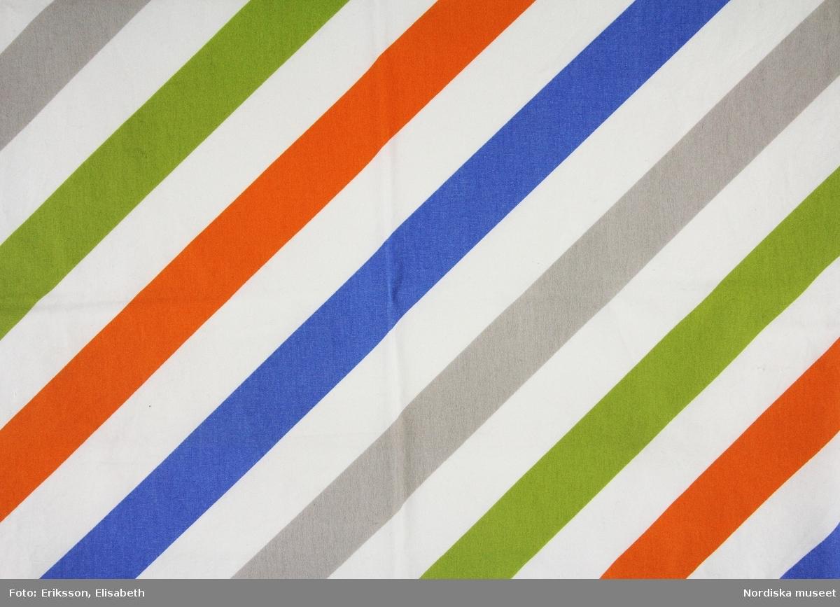 Mönster Avbilda, tryckta 5,5 cm breda diagonalränder i orange, grönt, grått och blått på vit botten. Formgivare Tom Hedqvist.