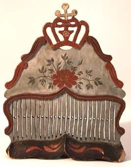 Bandvävsked av trä. På överstycket finns en genombruten krona, Bandgrinden är målad i grått och rött med blomsterornering på överstycket i rött, grågrönt och vitt. I skeden sitter ränning av rött och vitt garn.