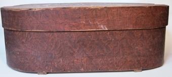 Stor oval ask med lock av träspån. Hel botten och svepet är fastsatt med träplugg. Svepändarna är fästade med stygn av rottågor. Botten är spräckt och lagad med en trälist samt förstärkt på undersidan med 2 lister. Lock, hel översida med svepet fastsatt med träplugg och svepändarna fästade med stygn av rottågor. Locket är spräckt och lagat med infällda trästycken. Undersidan är förstärkt med två spikade lister. Asken är målad rödbrun med dekoration i färgerna vitt, blått, grönt och gult. Köpt av  kopparslagare K. Nygren, Hudiksvall.
